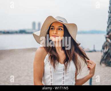Pretty woman wearing white dress and pamela hat standing - Stock Image