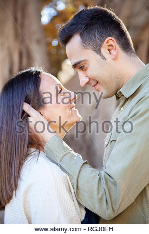 A young couple in love flirts in a public park at daylight in an European city - Stock Image