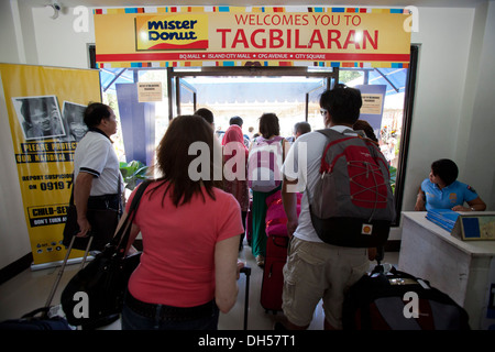 Travelers exiting the arrivals terminal at Tagbilaran Aiport in Bohol, Philippines. - Stock Image