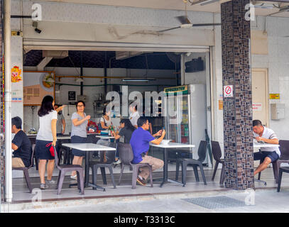 Locals eating at restaurant in Choo Chiat Singapore. - Stock Image