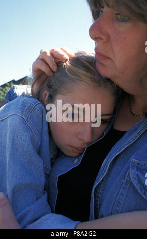 angry looking woman consoling, holding, protecting teenage girl - Stock Image