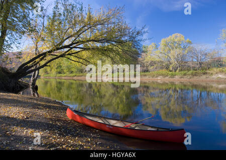 A canoe rests on the banks of he Connecticut River in Maidstone, Vermont. - Stock Image