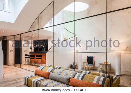 Sofa against mirrored wall in retro living room - Stock Image
