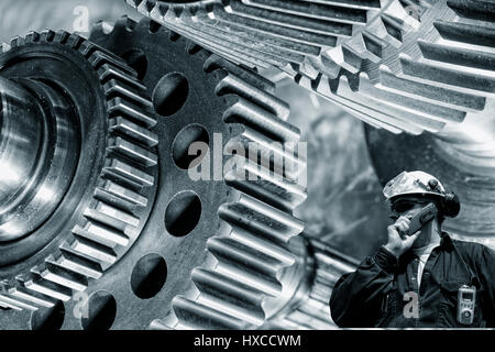 industry worker talking in phone with large machinery in steel industry - Stock Image