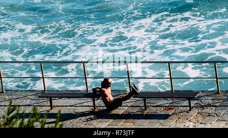 Cascais beach, Lisbon, Portugal - Dec 6, 2018: Middle aged athlete man exercises shirtless in between benches using his own weight. Waves crashing - Stock Image