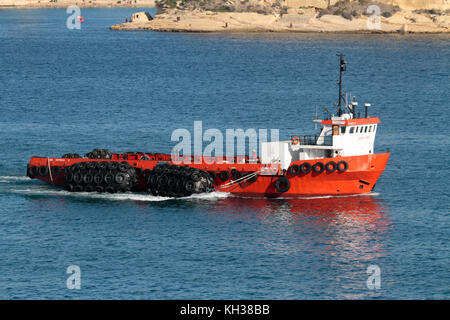 The offshore supply ship Sea Express III towing a set of pneumatic rubber marine fenders as it enters harbor in - Stock Image