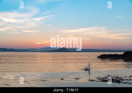 Penzance, Cornwall, UK. 28th Mar, 2019. UK Weather. A pair of swans were out on the sea at Penzance at sunrise this morning, with a misty St Michaels Mount in the background. Credit: Simon Maycock/Alamy Live News - Stock Image
