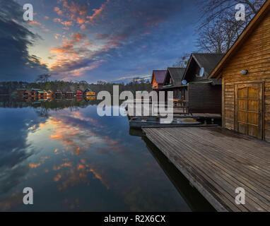 Tata, Hungary - Beautiful sunset over lake Derito (Derito to) in November with wooden fishing cottages and colourful sky and clouds - Stock Image