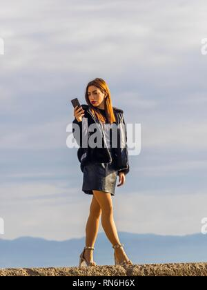 Pretty teen girl standing against sky looking at mobile cell-phone reading sms message - Stock Image