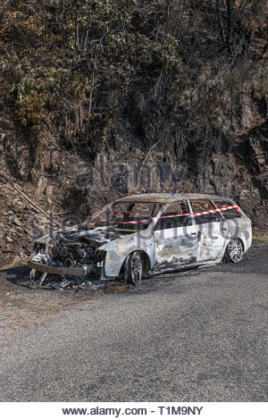 Burned car abandoned at roadside - Stock Image