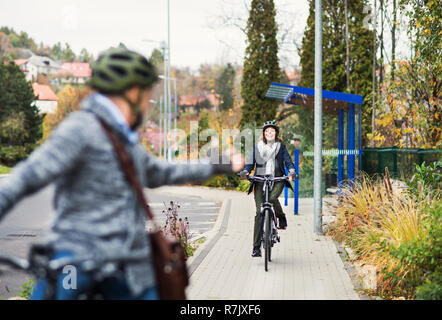 An active senior couple with helmets and electrobikes cycling outdoors on a pathway in town. - Stock Image