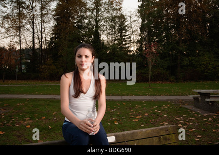 Portrait of a young woman in fitness attire holding a plastic disposable water bottle in a park setting. - Stock Image
