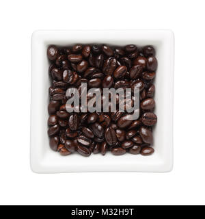 Roasted coffee beans in a square bowl isolated on white background - Stock Image