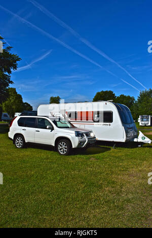 Modern car and caravan outfit at the Caravan & Motorhome Club site at Morn Hill, on the outskirts of Winchester. Sunny day with clear blue sky. - Stock Image