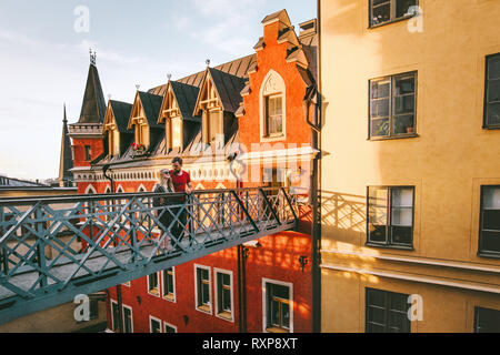 Hugging couple in love traveling together in Stockholm romantic vacations urban lifestyle architecture colorful houses european Sweden landmarks - Stock Image