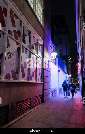 man and woman walk down allyway carying shopping bags at night, London, England, UK - Stock Image