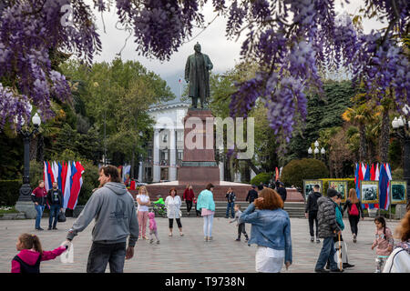 People walk during the may holidays near the monument to Vladimir Lenin, installed on the Lenin embankment in Yalta, Republic of Crimea - Stock Image