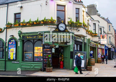 14 Decemberv2018 A patron leaving Quinn's Traditional Irish Pub in Newcastle County Down after a few bevvies on a mid winter afternoon - Stock Image