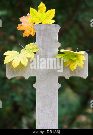 Leaves fall on a white cross on a cemetery in Frankfurt Main, Germany, 29 October 2007. Photo: Uwe Anspach - Stock Image