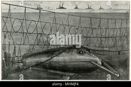 How the Untersee-Boot passes beneath the defensive nets which are hung at the entrance to harbours...      Date: 1915 - Stock Image