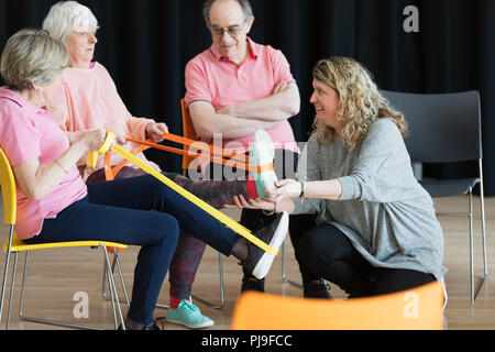 Instructor helping active seniors stretching legs, exercising with straps - Stock Image