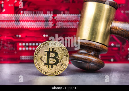 Bitcoin and gavel in front of computer mainboard.Concept image for cryptocurrency - Stock Image