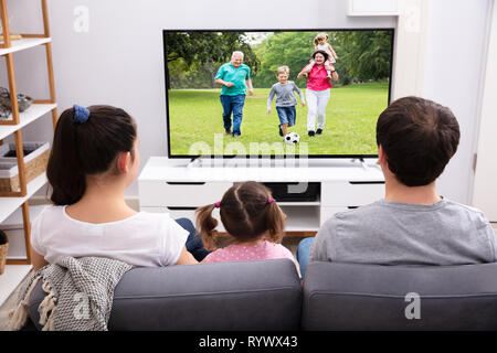 Rear View Of Parents Sitting With Her Daughter Watching Television At Home - Stock Image