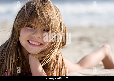 Young girl at the age of 6-7 paying at the beach - Stock Image