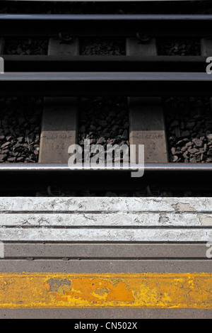 Yellow and white paint on platform of London train station and tracks and stones in background - Stock Image