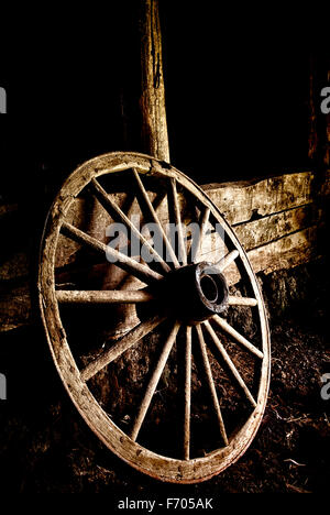 Wagon wheel leans on a post in a barn. - Stock Image