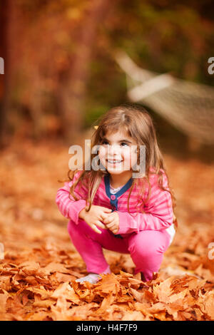 Nice little girl playing in autumn park, sweet kid sitting on the dry brown tree leaves, enjoying beauty of the - Stock Image
