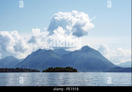 View of Lake Maggiore from Baveno Italy with Isola Madre and the mountains beyond.  Cumulus clouds and blue sky. - Stock Image