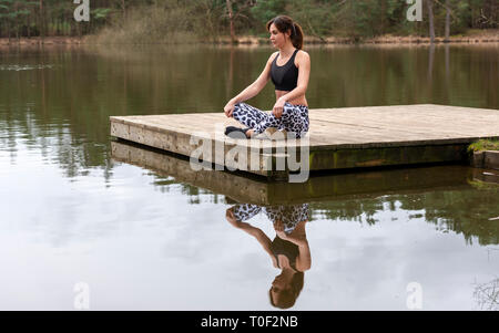 woman sitting on a jetty by a lake meditating - Stock Image