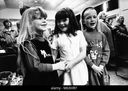 Young girls and audience singing Welsh national anthem at small eisteddfod in village hall at Y Groeslon Gwynedd - Stock Image