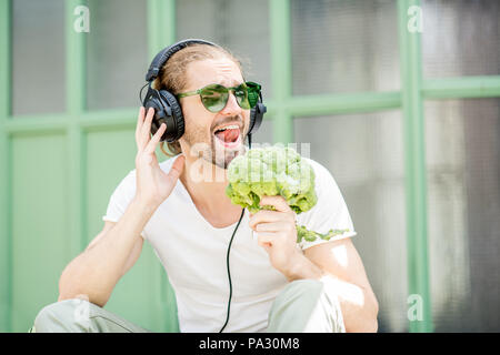 Funny portrait of a man listening to the music singing with broccoli outdoors on the green background - Stock Image