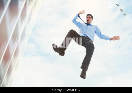 Stock image of businessman falling off a building - Stock Image