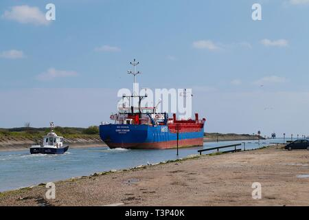 Rye, East Sussex, UK. 11th Apr, 2019. UK Weather: Sunny intervals with blustery winds on the Rye harbour nature reserve as a cargo ship followed by the harbour master heads out to sea from the river Rother. Credit: Paul Lawrenson 2019, Photo Credit: Paul Lawrenson/Alamy Live News - Stock Image