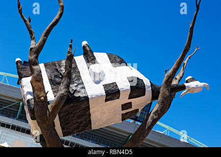 The Cow up a Tree sculpture in Melbourne Docklands.The Bovine themed sculpture was created in 1999 by the Australian artist John Kelly.It weighs four  - Stock Image