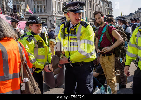 London, UK. 19th April 2019. Police carry away a person who has been arrested at at Extinction Rebellion's Sea of Protest after police surrounded the yacht and put a ring of officers around Oxford Circus. Police tried to persuade protesters to leave by threatening them with arrest. Later there were a number of arrests of protesters who refused to leave. A few tried to get the large crowd to protect the yacht, but XR organisers persuaded them not to physically oppose the police action. Peter Marshall/Alamy Live News - Stock Image