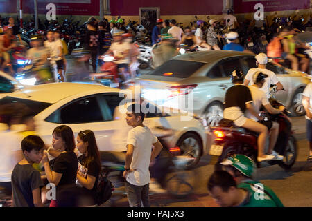 Motion blurred night shot of pedestrians waiting to cross road full of mopeds in busy street in Hanoi, Vietnam. The seemingly chaotic traffic scares t - Stock Image