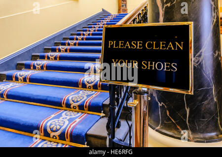Sign saying 'Please clean your shoes' at the bottom of a flight of stairs in a large, ornate building. - Stock Image