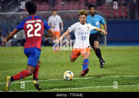 Johor Bahru, Malaysia. 24th Apr, 2019. Jin Jingdao (R) of Shandong Luneng shoots during AFC Champions League group match between Johor Darul Ta'zim and Shandong Luneng FC in Johor Bahru, Malaysia, April 24, 2019. Credit: Chong Voon Chung/Xinhua/Alamy Live News - Stock Image