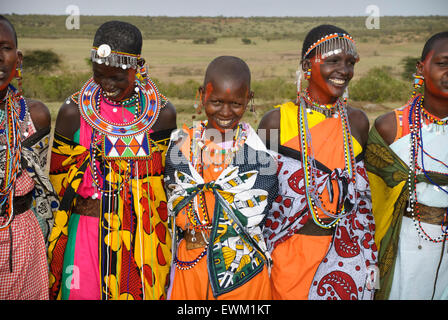 Masai women wearing colorful traditional dress, singing, laughing and smiling in a village near the Masai Mara, - Stock Image