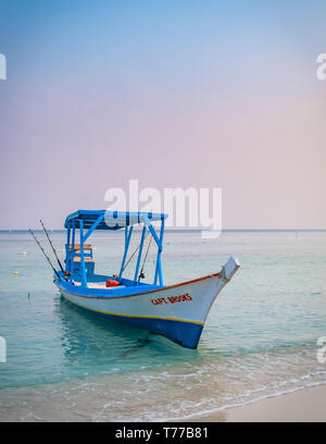 Small fishing boat available for hire photographed at dawn in West Bay Roatan Honduras. - Stock Image