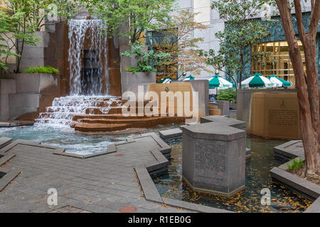CHARLOTTE, NC, USA-11/08/18: A small city park with a waterfall, and outside dining at Reid's in background. - Stock Image