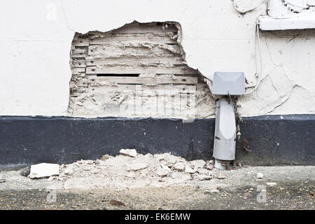 A damaged area on an external house wall with exposed plaster and wood - Stock Image