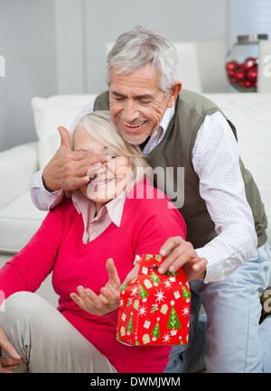Senior Man Covering Woman's Eyes While Giving Christmas Gift - Stock Image