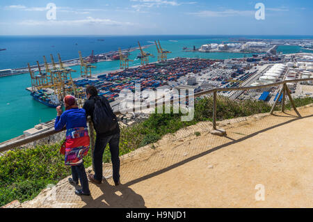 Couple looking at the container terminal of the port of Barcelona, Catalonia, Spain, from above. - Stock Image