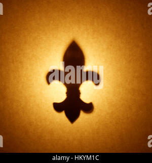 Backlit silhouette of fleur-de-lis shape cut out against brown tone paper, with spot highlight. - Stock Image