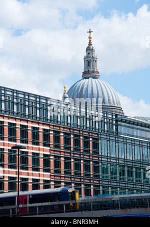 St Paul's Cathedral seen over modern buildings as a train goes past. - Stock Image